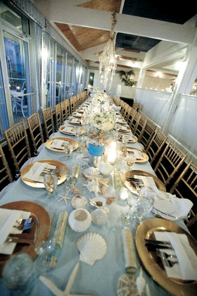 Long wedding reception table with gold place settings and seashells