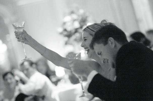Black and white image of couple toasting at reception