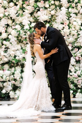 detroit lions taylor decker kisses wife bryn toyama at wedding, berta wedding gown, flower wall