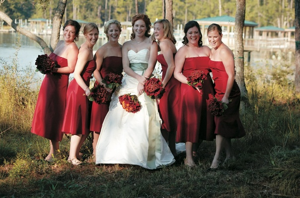 Bride in front of lake with bridesmaids in red bridesmaid dresses