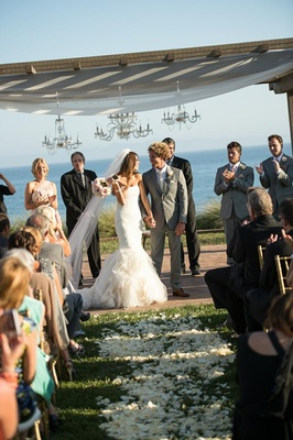 Bride and groom under chandelier chuppah at Terranea