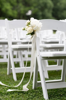 White ceremony chair with ribbon and flower details peony grass lawn outdoor ceremony