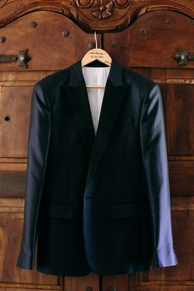 a grooms dark blue tuxedo jacket hanging up before ceremony