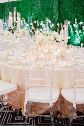 wedding reception with clear chiavari chairs, blush linens, ivory centerpiece with tapered candles
