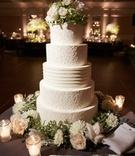 Wedding cake with design of bride's dress and fresh flowers at top and base gluten free