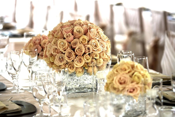 Wedding reception table is decorated with golden pink roses in crystal vases
