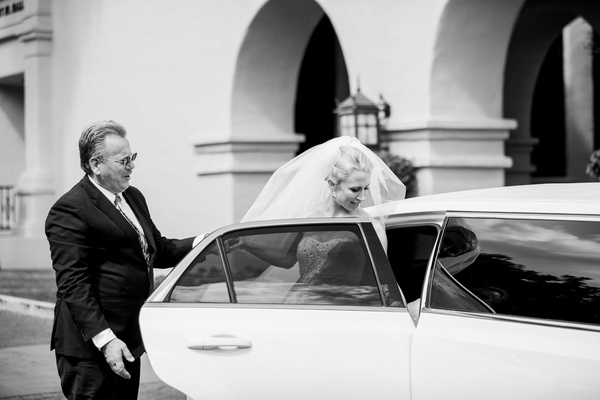 black and white photo of bride getting into limo with help from her father