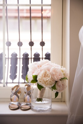 pretty bridal bouquet in glass vase next to silver shoes on windowsill