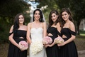 bride in nardos designs gown, bridesmaids in black fame & partner off-the-shoulder gowns with cutout