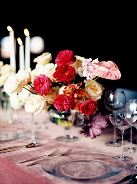 Centerpiece with white roses, red garden roses, and pink anthurium blossoms pink velvet linens wine