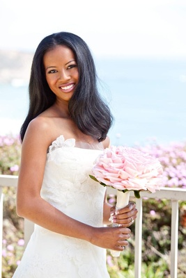 African American bride in white wedding dress with pink bouquet