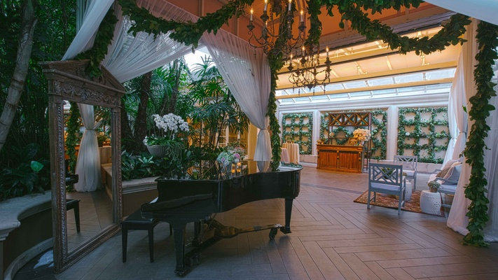 Grand piano next to rustic mirror, lounge area, garlands of greenery, chandeliers, trellis wall