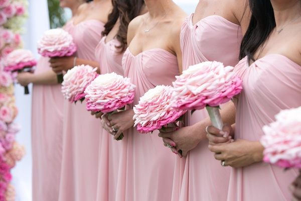 Bridesmaids in pink dresses carrying glamelia bouquet in pink