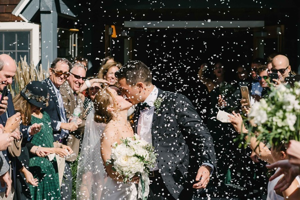 guests throw confetti newlyweds kiss outside church ceremony green maine wedding veil classic tuxedo