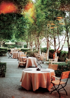 Tables covered in light orange tablecloths for a wedding cocktail hour at Marie Gabrielle's patio