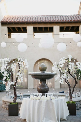 sweetheart table in front of fountain during daylight white flowers on trees and lanterns