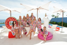 bridesmaids in floral robes by the pool with fun inner tubes pool floats