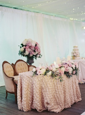 Sweetheart table with fabric flower linen, pink and white flowers, and antique loveseat