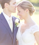 Bride in a lace Watters dress with cap sleeves with groom in royal blue suit