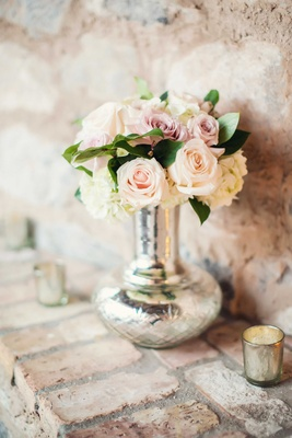 Stone wall with brick mantle, silver vase, metallic candle holder, pink rose, white hydrangea flower