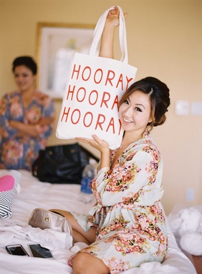 Bride in bridal suite with Hooray tote bag wearing flower print getting ready robe