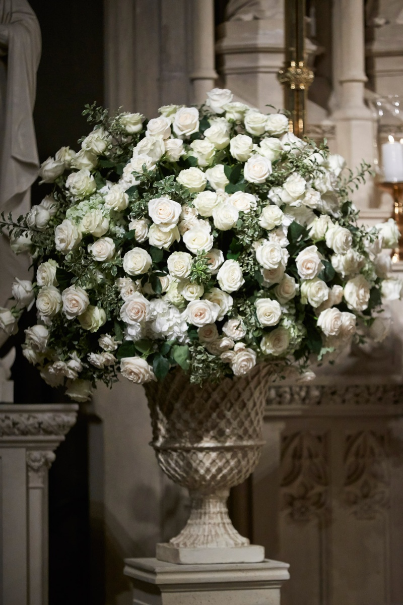 Wedding Ceremony Stone Urn Filled With White Flowers And Greenery At Altar