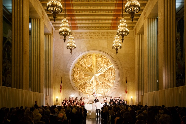 Bride and groom at altar gold texas emblem chandeliers overhead hall of state venue in texas dallas