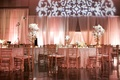 Wedding reception with peach draping, rosette tablecloths, and golden chairs
