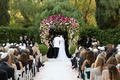 Wedding ceremony at the beverly hills hotel groom in white jacket pink white green wedding arch