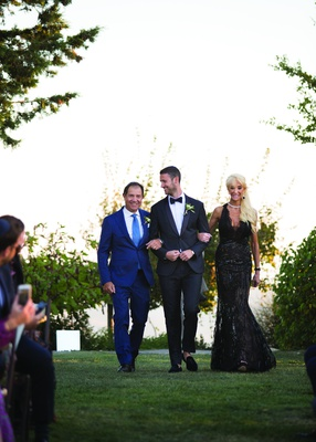 groom in classic black suit escorted down the aisle by father in blue suit and mother in black gown