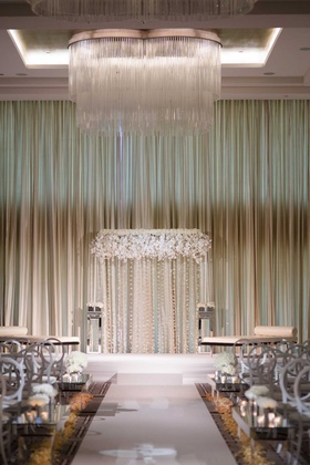 wedding ceremony chicago ballroom chandelier white flower round back chair and flower petals aisle