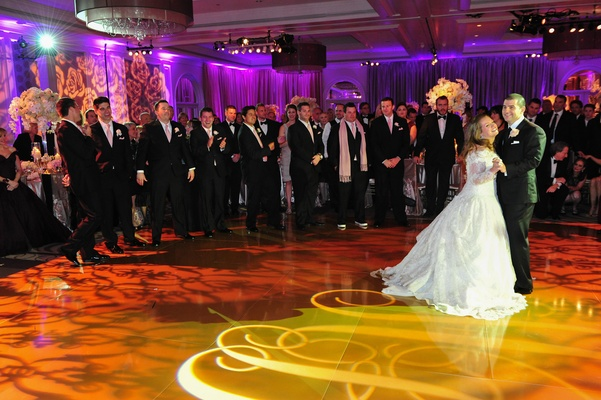 Wedding guests watch bride and groom dancing