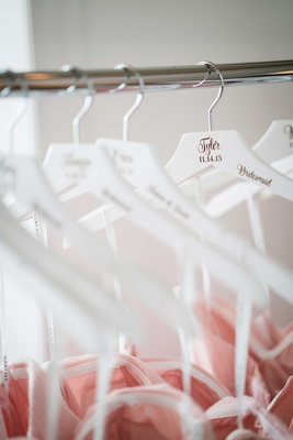 Personalized white bridesmaid hanger with blush dresses wedding date name and wedding title