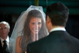 bride faces groom during ceremony wearing veil