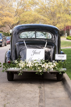 getaway car for dallas wedding reception greenery white flowers just married sign with ribbon