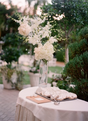 Outdoor Jewish wedding ceremony with a welcome table topped with guest book and yarmulke tray