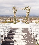 wedding ceremony on rooftop los angeles city view rustic chuppah arch white flower petal aisle chair