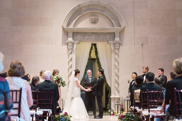 ceremony in great hall art institute of dayton venue wedding ohio fabric curtain greenery couple