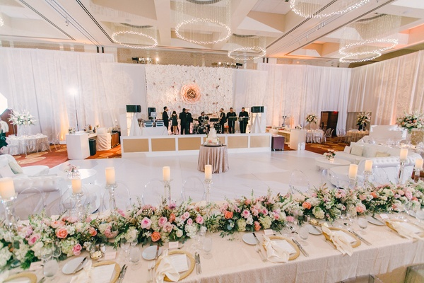 White dance floor with head table on one side, white lounge furniture, band stage with backdrop
