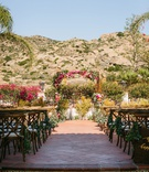 wedding ceremony outside hummingbird nest ranch terracotta tile pink greenery bougainvillea arch