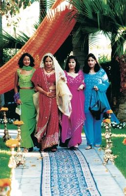 Bride walks down aisle with three bridesmaids