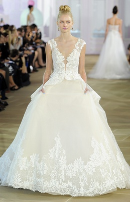 Sleeveless textured lace ball gown with plunging neckline, peplum overlay, and rich lace border.