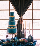 beauty beast movie styled wedding shoot blue gold cake lumiere candelabra clock rose glass case