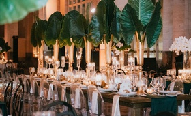 wedding reception emerald green color palette long table ghost chair with elephant ears, orchids