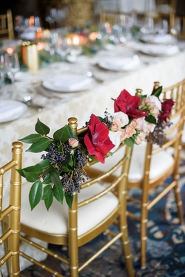 Wedding reception head table bride and groom chairs decorated with green leaves, red flowers