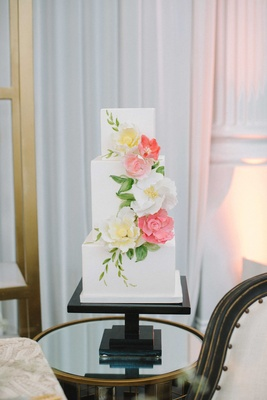 a square cake with three tiers featuring white yellow and pink floral detailing