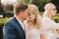Groom kisses bride's nose at wedding reception head table