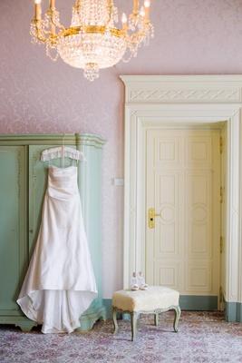 Wedding dress hanging in vintage villa room