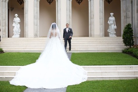 Bride in wedding dress illusion back details cathedral train approaching groom in grey suit