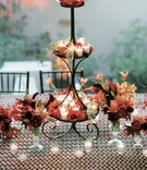Wrought iron tiered stand with candles and red flowers